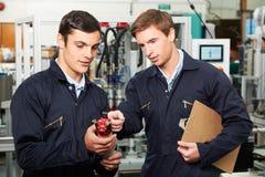 Инженер и тренирующая обсуждая компонент в фабрике Стоковые Фото