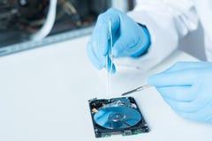 Инженер лаборатории работая на сломленном жёстком диске Стоковая Фотография