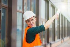 Инженер нося белый шлем указывает его рука для того чтобы показать строительную конструкцию стоковые изображения