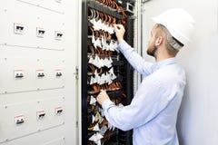 Инженер обслуживания в центре данных Работник в шлеме около переключателей оптических кабелей Стоковые Фото