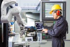 Инженер обслуживания используя управление портативного компьютера автоматическое Роба Стоковая Фотография