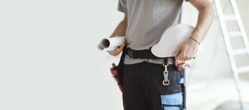 Инженер по строительству и монтажу держа шлем и проекты безопасности стоковые фото