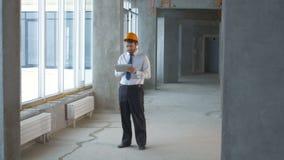 Инженер по строительству и монтажу, бизнесмен, риэлтор внутри нового здания проверяя строительную площадку используя таблетку видеоматериал