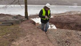 Инженер по строительству и монтажу используя ПК таблетки и идущ около канавы сток-видео