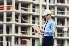Инженер по строительству и монтажу на строительной площадке смотря чертеж Стоковая Фотография RF