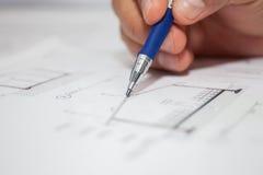 Инженер по строительству и монтажу рисует карандаш стоковая фотография
