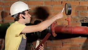 Инженер проверяет чтение манометра Работник одобряет чтения аппаратур Красивый мужской инженер акции видеоматериалы