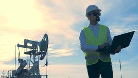 Инженер работает при компьтер-книжка, стоя на поле с нефтяными вышками акции видеоматериалы