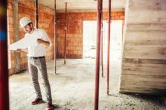инженер работая на строительной площадке, внутри внутренних кирпичных стен нося трудную шляпу и читая планы стоковая фотография