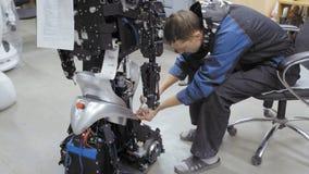Инженер работника на фабрике для продукции роботов Изобретает и создает новый робот Робот демонтирован сток-видео