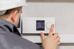 Инженер регулируя термостат для эффективной автоматизированной системы отопления Стоковое фото RF