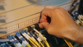 Инженер сети в комнате сервера работает с оптически patchcord и оптически модулем видеоматериал