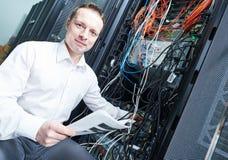 Инженер сети управляя в комнате сервера Стоковое Изображение