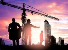 Инженер силуэта смотря рабочий-строителя под cran башни Стоковые Изображения