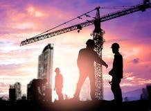 Инженер силуэта смотря рабочий-строителя под cran башни Стоковые Фотографии RF