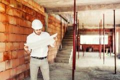 Инженер строительной промышленности работая на месте, планы чтения человека бумажные и наблюдая строительства стоковая фотография