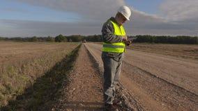 Инженер строительства дорог используя таблетку на дороге