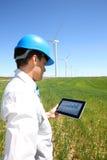 Инженер с таблеткой в поле ветротурбины Стоковая Фотография