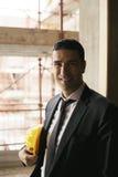 Инженер с шлемом в строительной площадке усмехаясь на камере, por Стоковые Фотографии RF