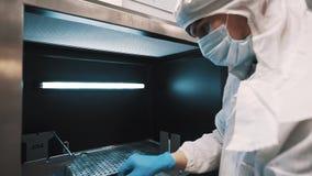 Инженер управляет объективами в коробке освещенной металлом на изготовлении сток-видео