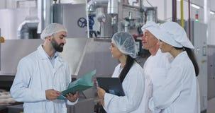 Инженер человека индустрии пекарни его шеф-повар помощи и хлебопека и молодая дама хлебопека имеет встречу, объяснять инженера че видеоматериал