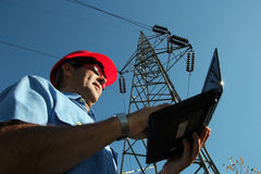 Инженер-электрик под высоковольтной башней стоковые фото