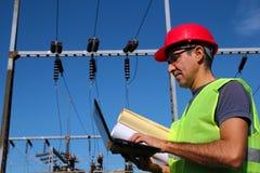 Инженер-электрик с компьтер-книжкой и светокопиями стоковое фото
