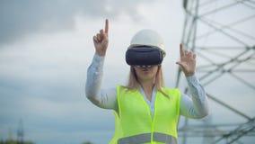 Инженер энергии среднего плана женский в стеклах виртуальной реальности и белый шлем на предпосылке высоковольтной силы видеоматериал