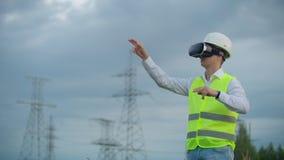 Инженер энергии среднего плана мужской в стеклах виртуальной реальности и белый шлем на предпосылке высоковольтной силы сток-видео