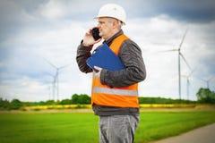 Инженер электрика говоря на умном телефоне около ветрянок Стоковая Фотография RF