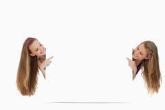 2 длинних женщины волос подпирают пустого знака Стоковые Изображения