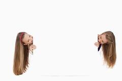 2 длинних молодой женщины волос за пустым знаком Стоковое Фото