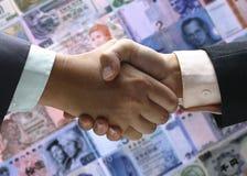 Иностранная валюта предпосылки встряхивания руки Стоковые Изображения RF