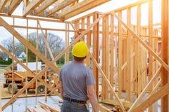 Инспектор по строительству выглядя домашней конструкцией на новом свойстве стоковое изображение