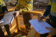 Инспектор проверяя перед вздохом работать на оценке степени риска разрешения JSA высоты на месте до выполнять рискованную работу стоковые фото