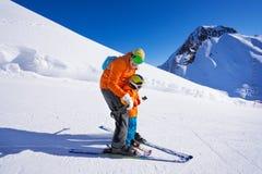 Инструктор дает урок лыжи к мальчику Стоковые Фотографии RF