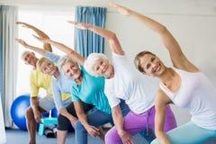 Инструктор выполняя йогу с старшиями Стоковые Фото