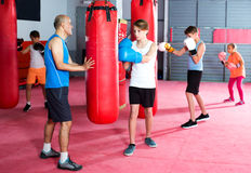 Инструктор и маленькие ребеята бокса практикуя дуновения Стоковые Фотографии RF