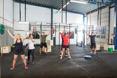 Инструктор помогая спортсменам в поднимаясь штангах Стоковое фото RF