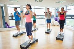 Инструктор при класс фитнеса выполняя тренировку аэробики шага с гантелями Стоковое Фото