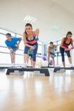 Инструктор при класс фитнеса выполняя тренировку аэробики шага с гантелями Стоковые Фотографии RF
