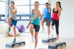 Инструктор при класс фитнеса выполняя тренировку аэробики шага Стоковая Фотография