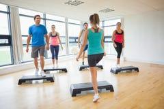 Инструктор при класс фитнеса выполняя тренировку аэробики шага Стоковые Фото