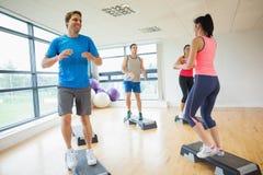 Инструктор при класс фитнеса выполняя тренировку аэробики шага Стоковое Изображение