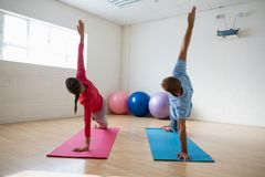 Инструктор при студент практикуя бортовое представление планки в студию йоги Стоковая Фотография