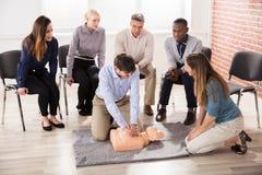 Инструктор скорой помощи показывая тренировку CPR на кукле стоковая фотография rf