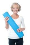 Инструктор спортзала держа голубую циновку тренировки Стоковые Изображения RF