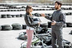 Инструктор с женщиной на следе с идет-karts стоковые изображения