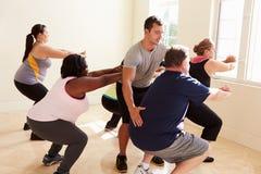 Инструктор фитнеса в классе тренировки для полных людей стоковое фото