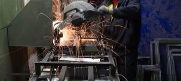 Инструментальный металл работника с точильщиком в мастерской фабрики меля искры утюга Стоковые Изображения